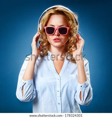 woman wearing headphones and pink  eyeglasses - stock photo