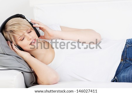 Woman wearing headphones listening to music lying on her back on a sofa with her eyes closed in enjoyment and appreciation