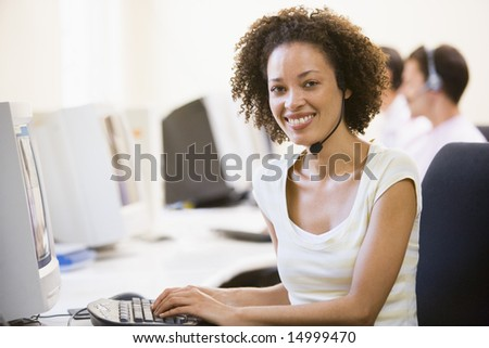 Woman wearing headset in computer room smiling - stock photo