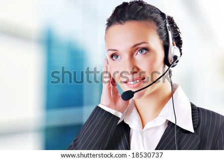 Woman wearing headset in office; could be receptionist - stock photo
