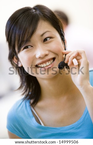 Woman wearing headset indoors smiling - stock photo