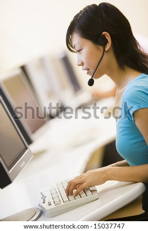 Woman wearing headset sitting in computer room typing - stock photo
