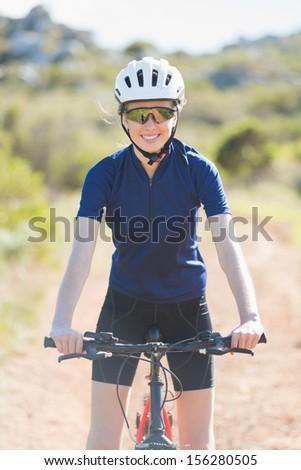 Woman wearing helmet on her bike looking at camera - stock photo