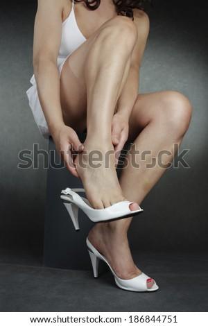 Woman wearing high heel shoes massaging  feet - stock photo