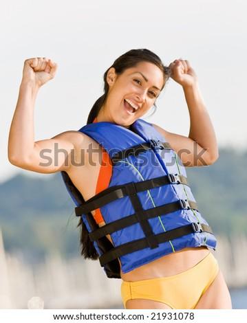 Woman wearing life jacket at beach - stock photo
