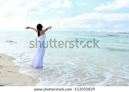 Woman wearing long white dress relaxing at the beach with arms open enjoying her freedom - stock photo