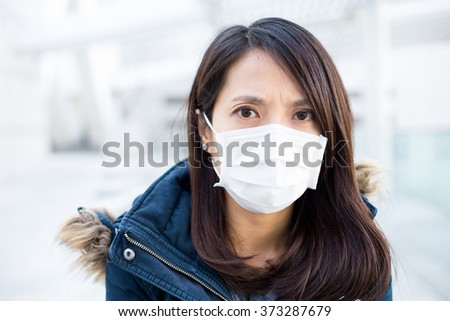 Woman wearing medical face mask for protection - stock photo