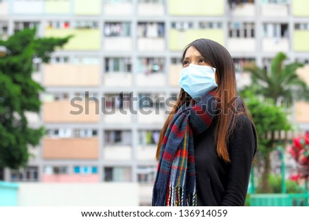 Woman wearing medical face mask in crowded city - stock photo