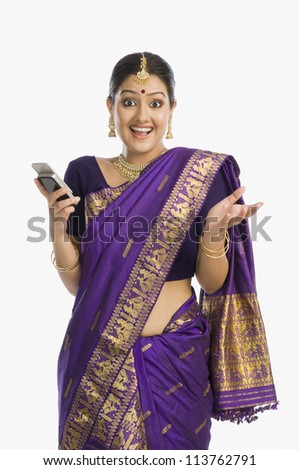 Woman wearing mekhla and text messaging on a mobile phone