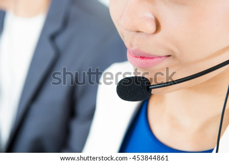 Woman wearing microphone headset as an operator (or telemarketer) - call center and customer service concepts