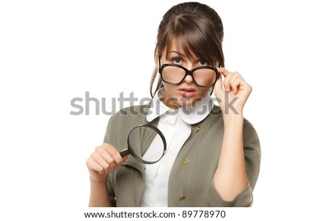 Woman wearing old fashioned eyeglasses holding magnifying glass for better magnification over white background - stock photo