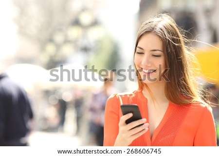 Woman wearing orange shirt texting on the smart phone walking in the street in a sunny day  - stock photo