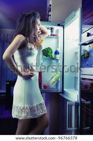 Woman wearing pajamas looking at fridge - stock photo