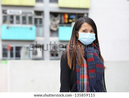 woman wearing protective face mask on street - stock photo