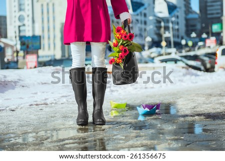 Woman wearing rain boots stay into a puddle - stock photo