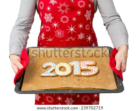 Woman wearing red apron holding home-made gingerbread cookies in shape of 2015 New Year digits on baking tray shot on white - stock photo