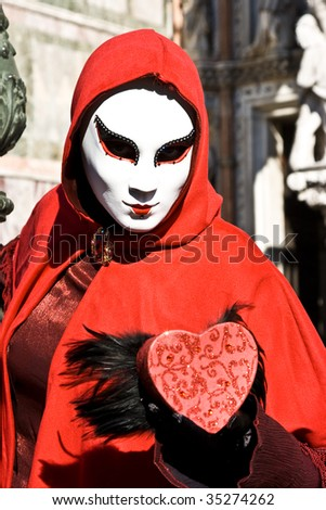 woman wearing red cape and white mask holding a red heart with wings