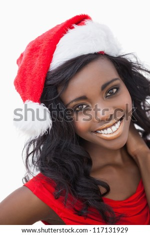 Woman wearing red dress and Santa Claus hat while smiling - stock photo