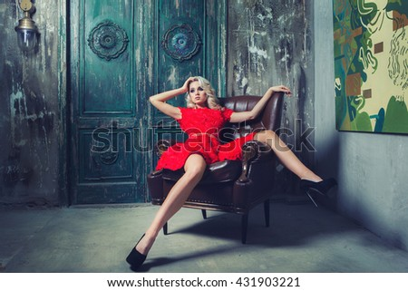 Woman wearing red dress freely sitting in armchair in interior - stock photo