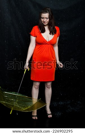 woman wearing red dress with umbrella stands under a rain - stock photo