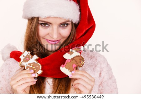 Woman wearing red hat holding delicious sweet gingerbread xmas cookies little snowman and santa claus. Happy girl awaiting christmas holidays