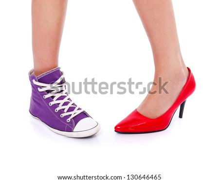 Woman wearing red high heel shoe on one leg and sport shoe on another leg - stock photo