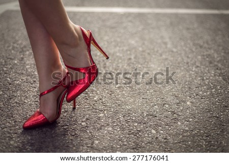 Woman wearing red high heel shoes. Exact focus on concrete. Copy space - stock photo