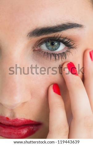 Woman wearing red lipstick and nail polish while touching her face - stock photo