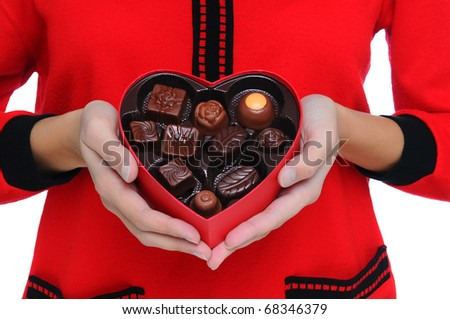 Woman wearing red sweater holding a Box Heart of Valentines Day Candy in front of her torso. Close shot in horizontal format. - stock photo