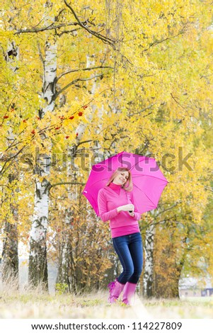 woman wearing rubber boots with umbrella in autumnal nature - stock photo