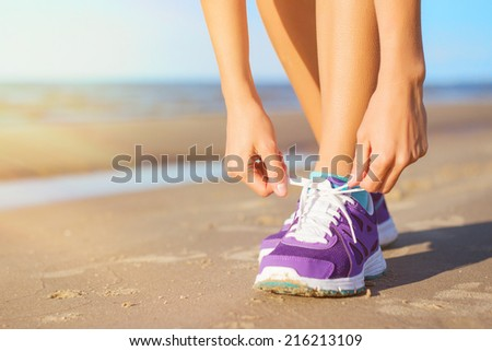 Woman wearing running shoes on the beach - stock photo