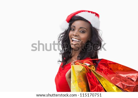 Woman wearing Santa Claus hat while holding bags