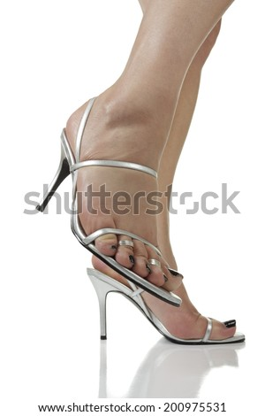 Woman wearing silver heels over white background - stock photo