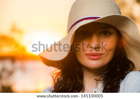 Woman wearing straw hat smiling and having fun against sunset and beautiful sea - stock photo