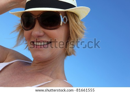 Woman wearing sunglasses and straw hat - stock photo