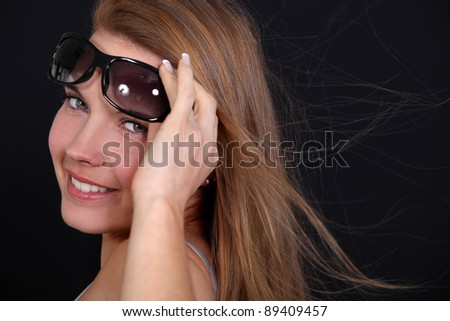 Woman wearing sunglasses on a breezy day - stock photo