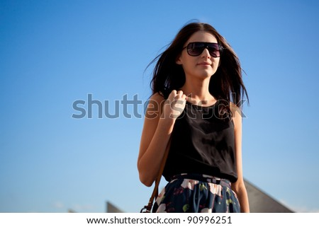 woman wearing sunglasses walking away over  blue sky