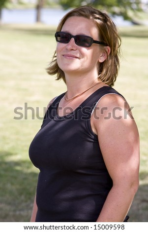 Woman wearing sunglasses with a happy expression - stock photo