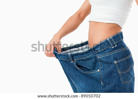 Woman wearing too large pants against a white background - stock photo