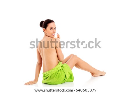 Woman wearing towel sitting on the floor, back view.