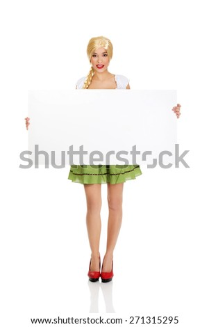 Woman wearing traditional Bavarian dress holding empty banner. - stock photo