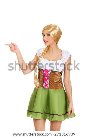 Woman wearing traditional Bavarian dress pointing aside. - stock photo