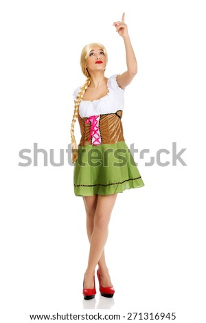 Woman wearing traditional Bavarian dress pointing up. - stock photo
