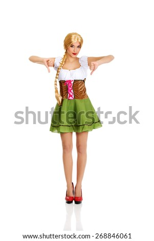 Woman wearing traditional Bavarian dress with thumbs down. - stock photo