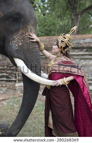woman wearing typical thai dress with thai style temple background, identity culture of thailand - stock photo