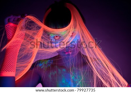 Woman wearing UV contacts, with UV makeup and hair, real shot under black light