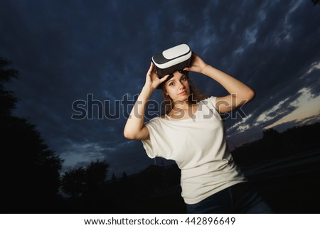 Woman wearing virtual reality goggles outside in spring nature. Beautiful girl in white on a background of clouds and sunset.