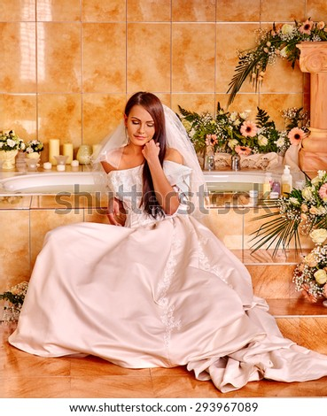 Woman wearing wedding dress relaxing at spa. - stock photo