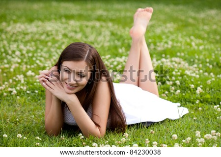 woman wearing white dress laying on grass in park - stock photo