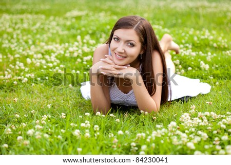 woman wearing white dress laying on grass in park